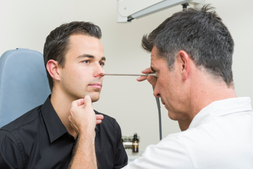 doctor examining nose of patient