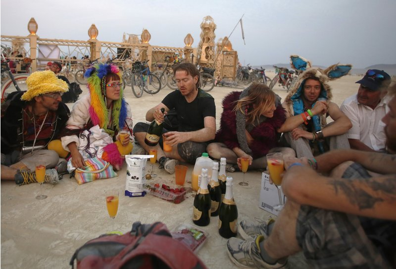 "Participants enjoy drinks before sunrise at the Temple of Grace during the Burning Man 2014 ""Caravansary"" arts and music festival in the Black Rock Desert of Nevada, August 29, 2014."