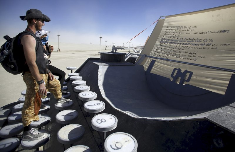 """Matt Steele (L) and Soroya Rowley read the poem on the Blunderwood Portable art installation during the Burning Man """"Carnival of Mirrors"""" arts and music festival in the Black Rock Desert of Nevada, September 4, 2015."""
