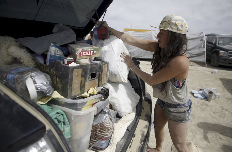 "Anna Kallett packs her car before departing during the Burning Man 2015 ""Carnival of Mirrors"" arts and music festival in the Black Rock Desert of Nevada, September 6, 2015. Sunday marks the last day of the sold-out festival that gathered approximately 70,000 people from all over the world."